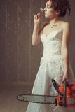Bloody bride. Pretty bride with bloody chainsaw smelling a chamomile in the empty room stock photos