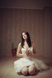 Bloody bride. Pretty bride sitting with flowers on the floor in the empty vintage room royalty free stock image