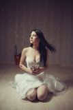 Bloody bride. Pretty seductive bride with flowers sitting on the floor in the empty room stock photo