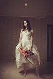 Bloody bride. Seductive bloody bride with chainsaw. Indoors shooting stock image
