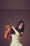 Bloody bride. Seductive bride with bloody chainsaw. Indoors shooting stock images