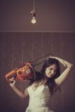 Bloody bride. Seductive bride with bloody chainsaw. Indoors shooting stock image