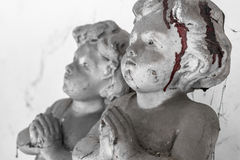 Bloody child statue. Statue of a child praying, covered with cobwebs and dried blood. Defocused blurry background Stock Photo