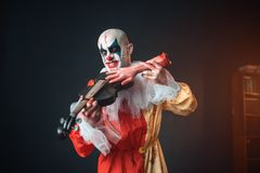 Bloody clown plays the violin with a human hand royalty free stock images