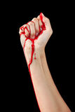 Bloody Fist. A red paint soaked hand making a fist isolated on black Royalty Free Stock Photography