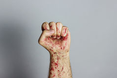 Bloody fist raising up in front of grey background Royalty Free Stock Images