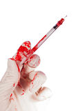 Bloody gloved hand holding a syringe Stock Photos