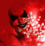 Bloody Grinning Clown. Sinister grinning clown behind a layer of bloodstained texture Royalty Free Stock Photography