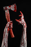 Bloody Halloween theme: bloody hand holding a bloody butcher's ax isolated on black background in studio Royalty Free Stock Photos
