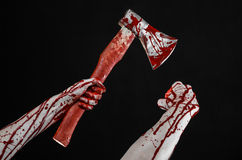 Bloody Halloween theme: bloody hand holding a bloody butcher's ax isolated on black background in studio Stock Photography