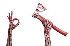 Bloody Halloween theme: bloody hand holding a bloody butcher's ax isolated on white background in studio Royalty Free Stock Images