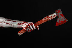 Bloody Halloween theme: bloody hand holding a bloody butcher's ax isolated on white background in studio Stock Images