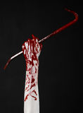 Bloody Halloween theme: bloody hand holding a bloody crowbar isolated on a black background Stock Photo