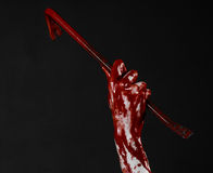 Bloody Halloween theme: bloody hand holding a bloody crowbar isolated on a black background Royalty Free Stock Image