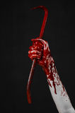 Bloody Halloween theme: bloody hand holding a bloody crowbar isolated on a black background Stock Photography