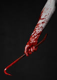 Bloody Halloween theme: bloody hand holding a bloody crowbar isolated on a black background Royalty Free Stock Photos
