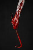Bloody Halloween theme: bloody hand holding a bloody crowbar isolated on a black background Stock Photos