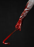 Bloody Halloween theme: bloody hand holding a bloody crowbar isolated on a black background Royalty Free Stock Photography