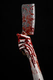Bloody Halloween theme: bloody hand holding a large bloody kitchen knife on a black background isolated Royalty Free Stock Photos