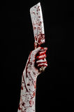 Bloody Halloween theme: bloody hand holding a large bloody kitchen knife on a black background isolated Stock Images