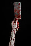 Bloody Halloween theme: bloody hand holding a large bloody kitchen knife on a black background isolated Royalty Free Stock Image