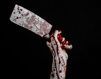 Bloody Halloween theme: bloody hand holding a large bloody kitchen knife on a black background isolated Royalty Free Stock Photo