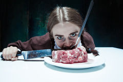 Bloody Halloween theme: crazy girl with a knife, fork and meat Stock Photo