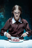 Bloody Halloween theme: crazy girl with a knife, fork and meat Stock Image