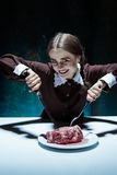 Bloody Halloween theme: crazy girl with a knife, fork and meat Royalty Free Stock Image