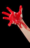 Bloody Hand. A red paint covered hand reaching out isolated on black Stock Images