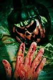 Bloody hand and Halloween jack-o'-lantern. Closeup of a bloody hand and a scary Halloween jack-o'-lantern Stock Photos