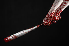 Bloody hand holding a baseball bat, a bloody baseball bat, bat, blood sport, killer, zombies, halloween theme, isolated, black bac Royalty Free Stock Images