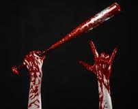 Bloody hand holding a baseball bat, a bloody baseball bat, bat, blood sport, killer, zombies, halloween theme, isolated, black stock image