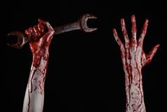 Bloody hand holding a big wrench, bloody wrench, big key, bloody theme, halloween theme, crazy mechanic, black background Royalty Free Stock Photos