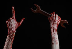 Bloody hand holding a big wrench, bloody wrench, big key, bloody theme, halloween theme, crazy mechanic, black background Stock Photo