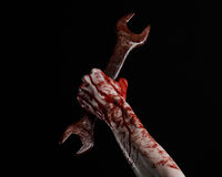 Bloody hand holding a big wrench, bloody wrench, big key, bloody theme, halloween theme, crazy mechanic, black background Stock Photography