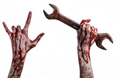 Bloody hand holding a big wrench, bloody wrench, big key, bloody theme, halloween theme, crazy mechanic, white background Stock Photo