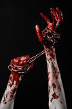Bloody hand holding chain, bloody chain, halloween theme, black background, isolated Stock Photo