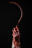 Bloody hand holding a sickle, sickle bloody, bloody scythe, bloody theme, halloween theme, black background, isolated Stock Photo