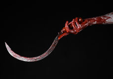 Bloody hand holding a sickle, sickle bloody, bloody scythe, bloody theme, halloween theme, black background, isolated. Psycho, thug, a bloody knife, bloody Stock Images