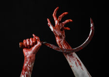 Bloody hand holding a sickle, sickle bloody, bloody scythe, bloody theme, halloween theme, black background, isolated Royalty Free Stock Image