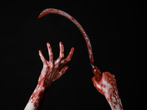 Bloody hand holding a sickle, sickle bloody, bloody scythe, bloody theme, halloween theme, black background, isolated Stock Photos