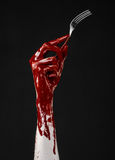 Bloody hand holding a spoon, fork, halloween theme, bloody spoon, fork, black background, isolated Royalty Free Stock Photos