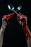 Bloody hand holding a spoon, fork, halloween theme, bloody spoon, fork, black background, isolated Stock Photography