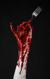 Bloody hand holding a spoon, fork, halloween theme, bloody spoon, fork, black background, isolated Royalty Free Stock Images