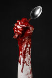 Bloody hand holding a spoon, fork, halloween theme, bloody spoon, fork, black background, isolated Stock Photo