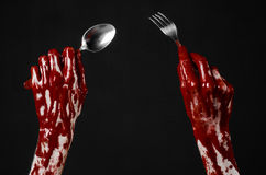 Bloody hand holding a spoon, fork, halloween theme, bloody spoon, fork, black background, isolated Stock Image