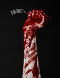Bloody hand holding a spoon, fork, halloween theme, bloody spoon, fork, black background, isolated Royalty Free Stock Photo