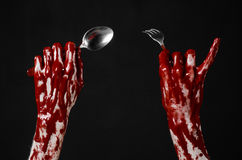 Bloody hand holding a spoon, fork, halloween theme, bloody spoon, fork, black background, isolated Royalty Free Stock Image