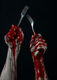 Bloody hand holding a spoon, fork, halloween theme, bloody spoon, fork, black background, isolated Stock Photos